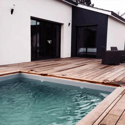 Piscine maçonnée avec marches en angle, terrasse bois